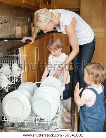 Family standing besides the dishwaser in the kitchen - stock photo