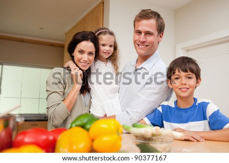 Family standing in the kitchen together