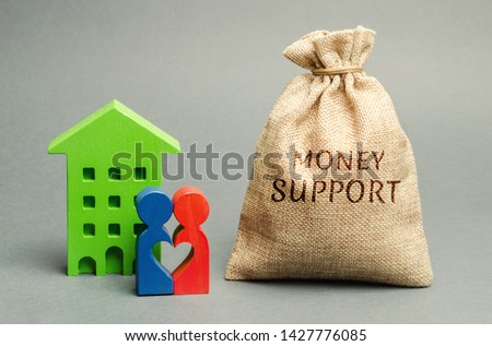 Family standing near the house with a bag with the word Money support. Financial assistance to support young families. Stimulating demographic growth. Soft loans and tax breaks for buying a new home