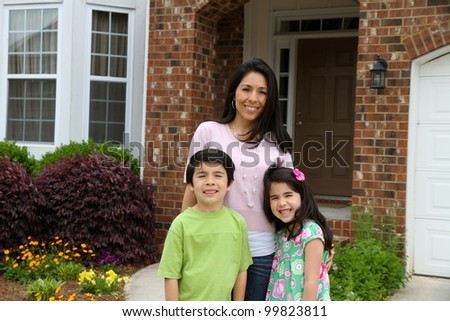 Family standing outside their home in summer