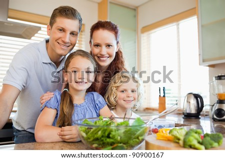 Family standing together behind the kitchen counter - stock photo