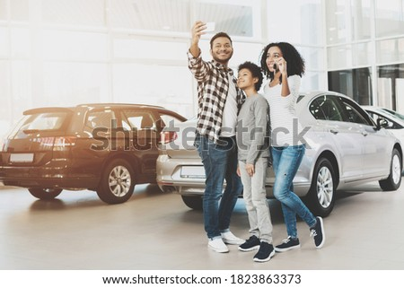 Family stands in a car dealership and takes a selfie on the phone. A young family bought a new car at a large car dealership. Stock foto ©