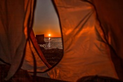 Family summer getaway. Beautiful sunrise on the wild sea beach at campsite at summer. Healthy lifestyle, green local tourism and safe vacations, mental recreation, focus on sun, view from camping tent