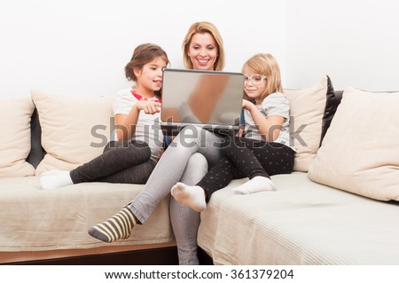 Family surfing or browsing internet together using laptop relaxed on the sofa or couch #361379204