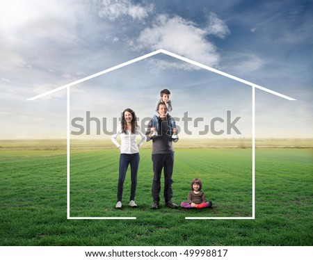 Family surrounded by the form of a house on a green meadow