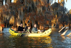 Family swims on an inflatable boat among the autumn bald cypresses.  Louisiana, Lake Martin, US