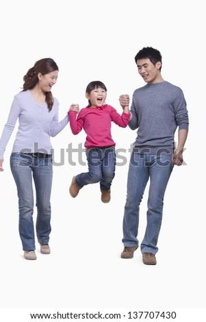 Family swinging child in mid-air, studio shot