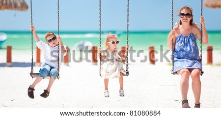 Family swinging with tropical beach on background