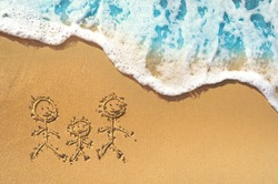 Family symbol - mother, father, child drawing on the sand on a golden sunny sandy beach in resort on summer vacation rest. Background  with soft waves with foam blue ocean sea.