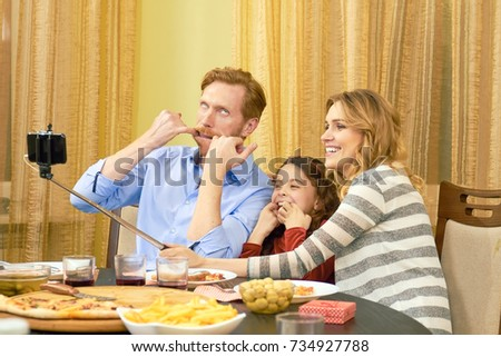 Family taking a funny selfie. Parents with daughter having dinner.