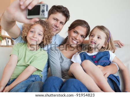 Family taking a photo of themselves in their living room