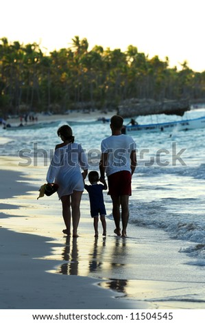 Family taking a walk on a sandy beach of tropical resort
