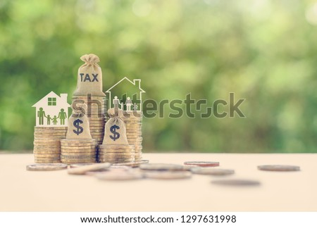 Family tax benefit / residential property or estate tax concept : Tax burlap bag, family members, house on rows of coin money, depicts mandatory financial charge / type of levy imposed upon a taxpayer