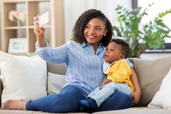 family, technology and motherhood concept - happy smiling young african american mother with little baby son taking selfie by smartphone at home