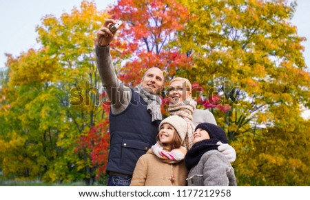 family, technology and people concept - happy mother, father, daughter and son taking selfie by camera over autumn park background