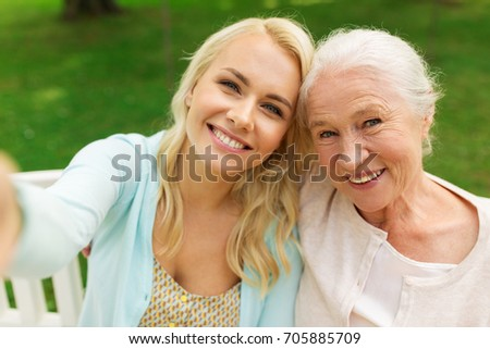 family, technology and people concept - happy smiling young daughter and senior mother sitting on park bench and taking selfie