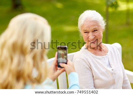 family, technology and people concept - young daughter with smartphone photographing her happy smiling senior mother at park