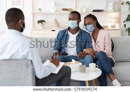 Family Therapy During Pandemic. Happy Black Couple In Protective Masks Sitting On Couch At Counselor's Office, Listening Advices, Selective Focus