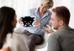 Family Therapy. Psychologist Testing Couple Showing Inkblot Picture During Psychotherapy Session Sitting In Office. Selective Focus
