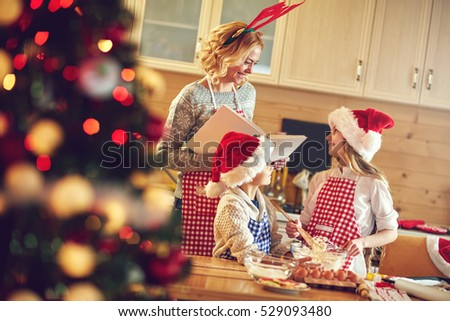 Family time- children and mother making Christmas cookies #529093480