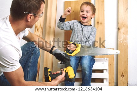 Family time: Dad shows his son hand tools, a yellow screwdriver and a hacksaw. They need to drill and drill boards for repair.