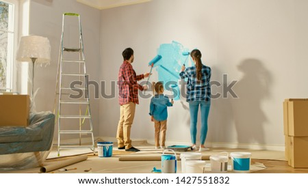 Family Time Together with Small Daughter. Young Father and Mother Showing Their Child How to Paint a Wall with a Roller. Paint Color is Light Blue. Room at Home is Prepared for Renovations. Foto stock ©