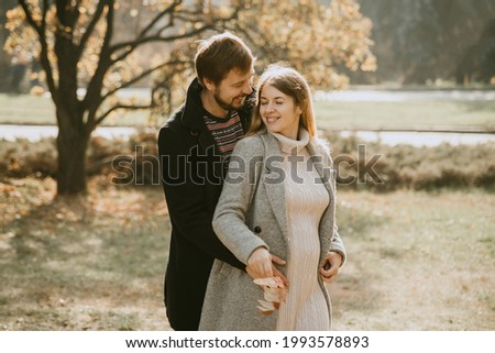 Family together in autumn park. Happy couple Husband and his pregnant wife relaxing in nature. happy married couple expecting baby. Pregnancy, maternity concept. Parents hands on pregnant belly