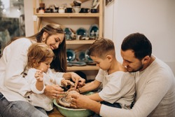 Family together manufacturing at a pottery class