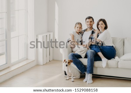 Family, togetherness and relationnship concept. Happy man embraces daughter and wife, sit on comfortable white sofa in empty room, their pet sits on floor, make family portrait for long memory #1529088158