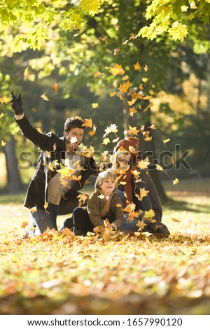 Family tossing autumn leaves in park in autumn