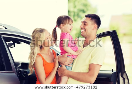 family, transport, leisure and people concept - happy man, woman and little girl with car laughing at home parking space
