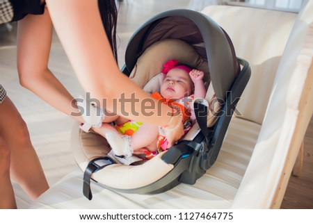family, transportation, security, car trip and people concept - happy mother fixing baby girl in baby seat at home #1127464775