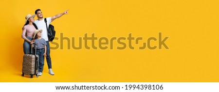 Family Travel Concept. Happy middle eastern parents with little daughter carrying suitcases and pointing aside at copy space on yellow background, mom, dad and child ready for vacation, panorama