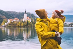 Family Travel Europe. Mother and child in yellow raincoats looking at Bled Lake. Autumn or Winter in Slovenia. View on Island with Church on Bled Lake with Castle and Mountains in Nature Background.