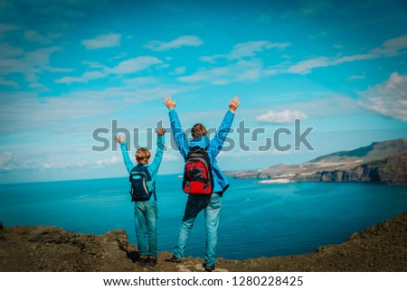 family travel - father and son hiking in mountains at sea #1280228425
