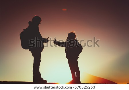 Family Travel Father And Son With Backpacks Hiking At Sunset 570525253