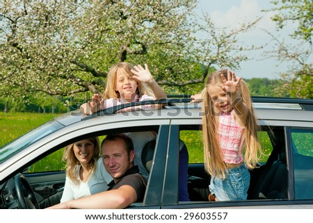 Family travelling by car, kids waving their hands