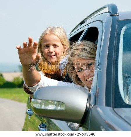 Family travelling by car, mother waving with hands