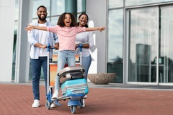 Family Trip Concept. Portrait of cheerful African American girl having fun and spreading hands, ready for vacation, standing on luggage cart. Parents walking with baggage trolley, riding daughter