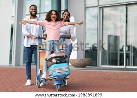Family Trip Concept. Portrait of cheerful African American girl having fun and spreading hands, ready for vacation, standing on luggage cart. Parents walking with baggage trolley, riding daughter Foto stock ©