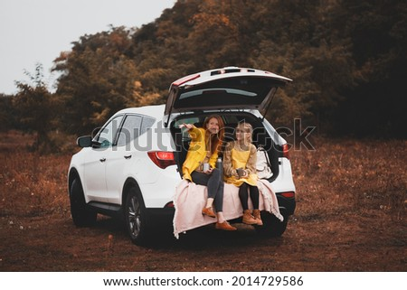 family trip - happy girls travel by car. mamma with daughter sitting in the boot and drinking tea Stockfoto ©