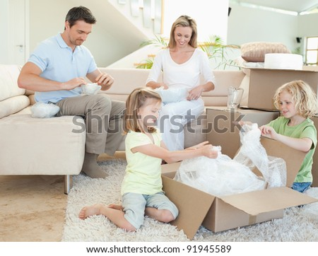 Family unpacking cardboard box together