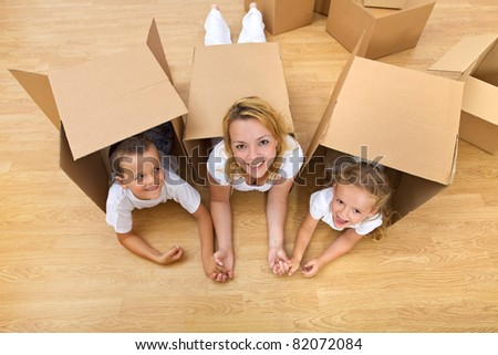 Family unpacking in a new home having fun on the floor - stock photo