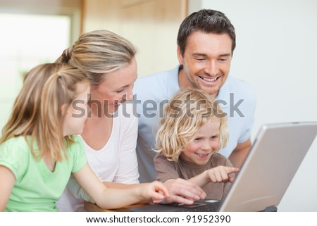 Family using notebook in the kitchen together