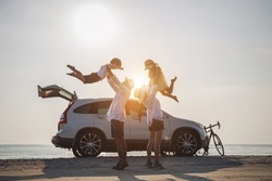 Family vacation holiday, Silhouette of the happy family on the evening beach. Father and mother are happily carrying their son and daughter on the beach, Car and bicycles in the back.
