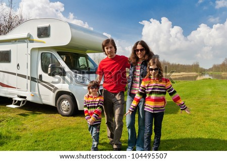 Family vacation in camping, camper trip. Happy active parents with kids travel on RV. Family having fun near their motorhome. Spring vacation trip with children.