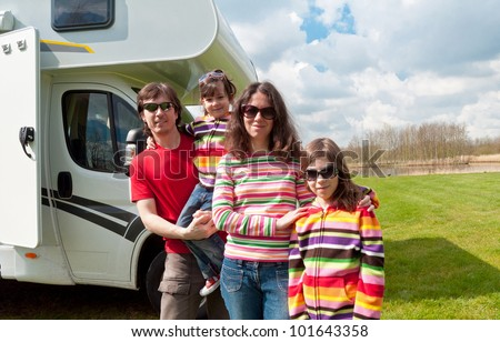 Family vacation in camping. Happy active parents with kids travel on camper (RV). Family having fun near their motorhome. Spring vacation trip with children.