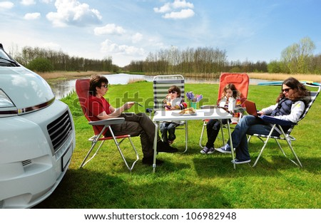 Family vacation in camping. Happy active parents with kids travel on camper (RV). Family having fun  and relaxing near their motorhome. Spring holiday trip with children.