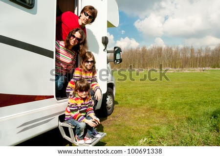 Family vacation in camping. Happy active parents with two kids travel on camper. Family having fun near their motorhome. Spring vacation trip with children.