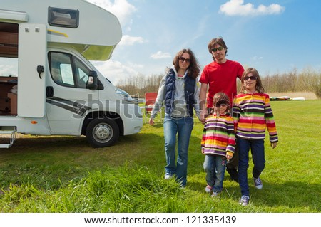 Family vacation in camping, holiday trip in camper. Happy active parents with kids travel on RV. Family having fun near their motorhome. Spring vacation trip with children.